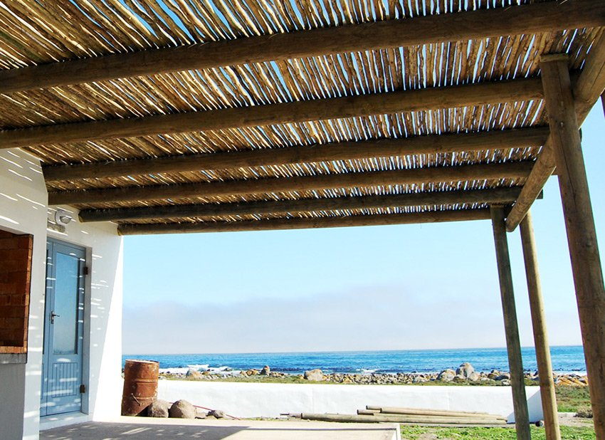 Wooden latte fencing used to build a patio roof at the seaside