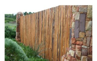 Rustic timber fence between stone pillars
