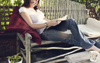 Woman sitting on a wooden garden bench reading a book. Coffee placed on a wooden garden table