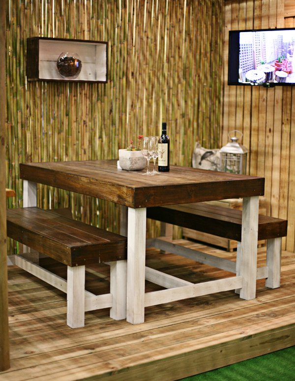 Table and bench set on a wooden deck enclosed with a wooden fence