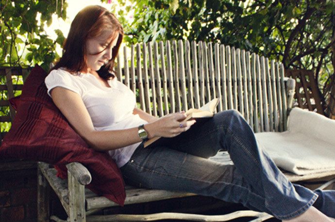 Woman sitting on a wooden garden bench reading a book