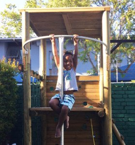 kid playing on a Pole Yard jungle gym
